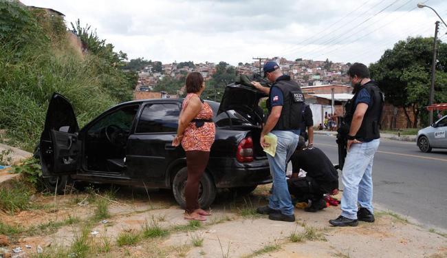 Policiais observam carro que era dirigido pela vítima - Foto: Edilson Lima | Ag. A TARDE | 29.10.2014