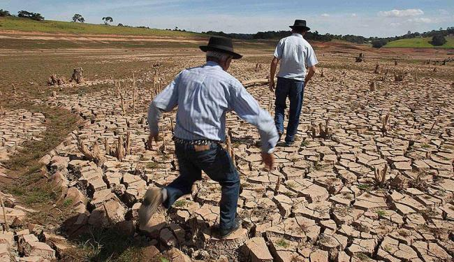 Homens caminham no leito seco do reservatório da Cantareira, em São Paulo - Foto: Rogerio Casemiro | Reuters