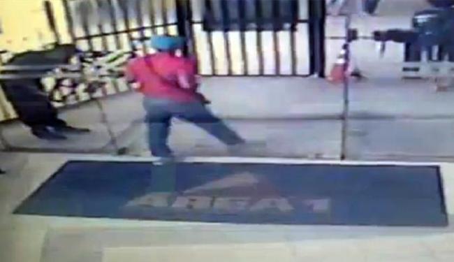 Adolescente, de camisa vermelha, aparece entrando pela portaria principal da faculdade - Foto: Reprodução