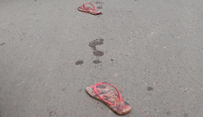 Sandálias da menina ficaram no asfalto após o crime - Foto: Edilson Lima | Ag. A TARDE