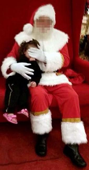 Papai Noel esconde rosto de criança com as mãos - Foto: Reprodução