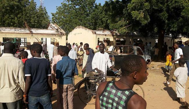 Parentes das vítimas e curiosos acompanham as notícias na frente da escola onde houve o atentado - Foto: Adamu Adamu | AP Photo