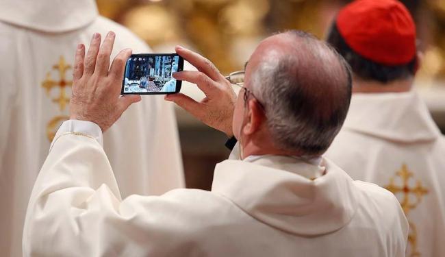 Os smartphones também já estão presentes nas missas - Foto: Remo Casilli | Agência Reuters