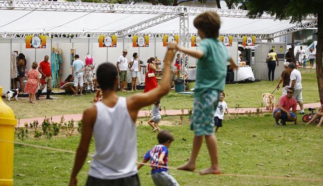 Na praça Ana Lúcia Magalhães, crianças brincam com estandes da feira ao fundo - Foto: Fernando Vivas | Ag. A TARDE | 06.12.2014