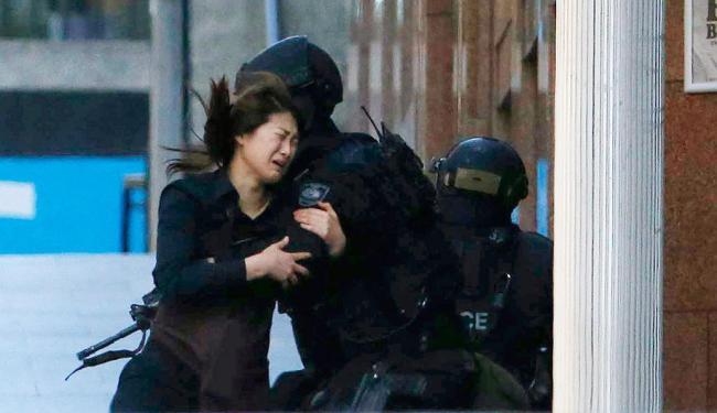 Mulher libertada corre em direção a um policial em frente ao local onde pessoas são mantidas reféns - Foto: Jason Reed   Agência Reuters