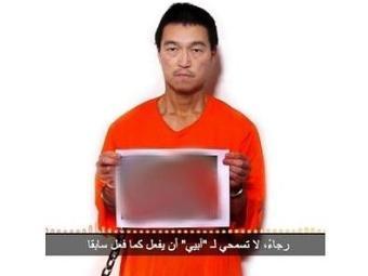 Refém japonês Kenji Goto segura imagem que seria de seu companheiro, Haruna Yukawa, morto - Foto: Reprodução l Twitter l @siteintelgroup