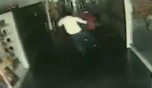 Frame de vídeo da segurança mostra comerciante (de branco) enfrentando bandido - Foto: Reprodução