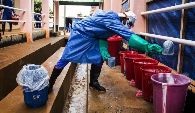 Trabalhador de saúde mistura cloro com a água em um centro de tratamento de Ebola em Serra Leoa - Foto: Michael Duff | AP Photo