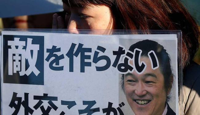 Mulher chora segurando cartaz com retrato do jornalista Kenji Goto durante manifestação no Japão - Foto: Toru Hanai | Agência Reuters