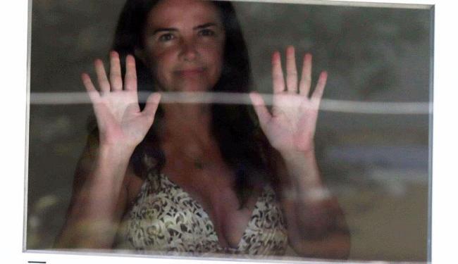 A ex-modelo aparece na janela da sua casa, enquanto agentes federais cumpriam os mandados - Foto: Fábio Motta | Estadão Conteúdo