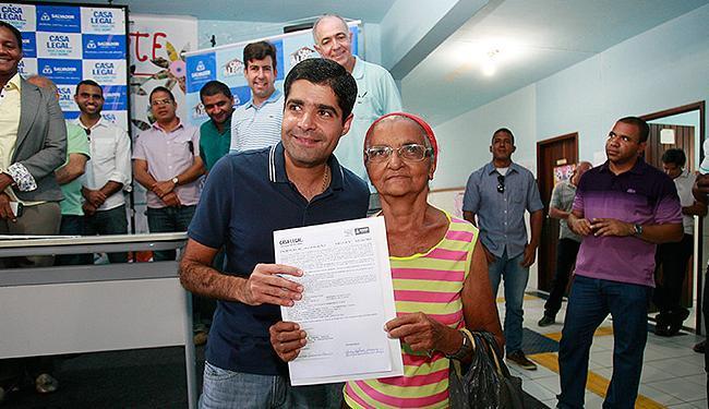 Prefeito entrega o título de posse a uma moradora - Foto: Luciano da Matta | Ag. A TARDE