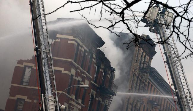 Bombeiros tentam apagar as chamas antes do desabamento - Foto: Agência Reuters