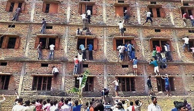Pais foram flagrados escalando paredes para passar cola aos filhos durante prova - Foto: Press Trust of India l AP
