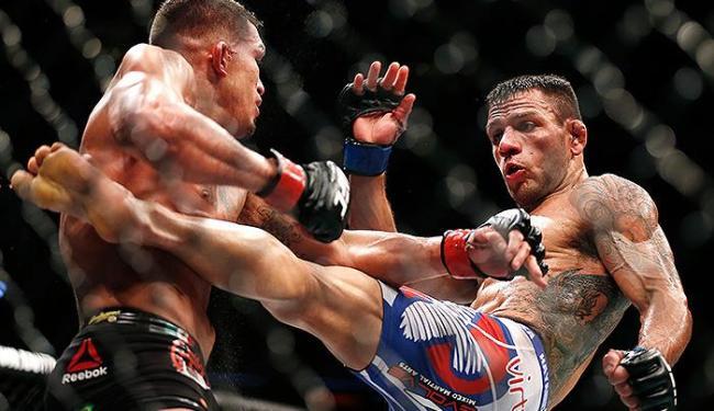Rafael dos Anjos (calção azul) exerce domínio sobre seu rival, o norte-americano Anthony Pettis - Foto: Brandon Wade l AP Photo