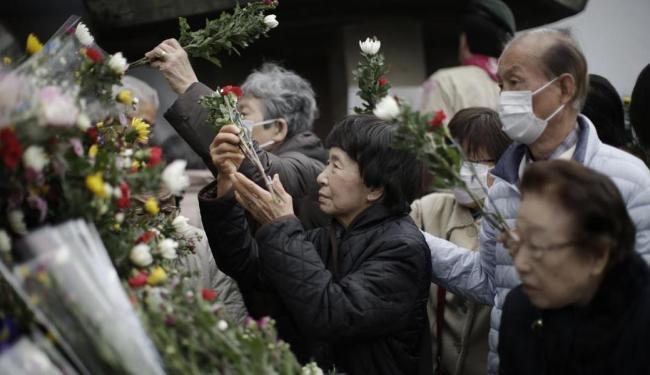 População deposita flores em um memorial aos mortos durante os bombardeios - Foto: Eugene Hoshiko | AP Photo