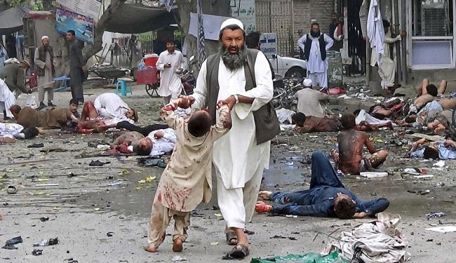 Um homem carrega um menino ferido após o ataque suicida - Foto: Pajwak | Ag. Reuters