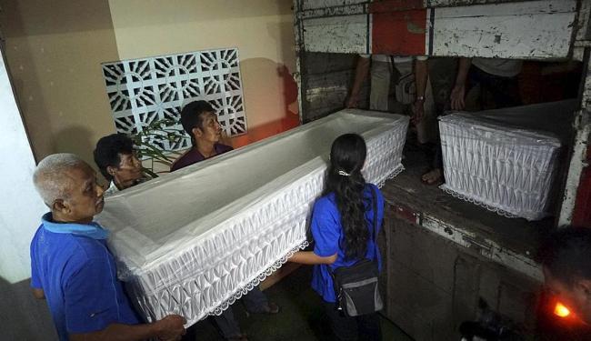 Funcionários transportam caixões que serão usados após execuções - Foto: Ag. Reuters
