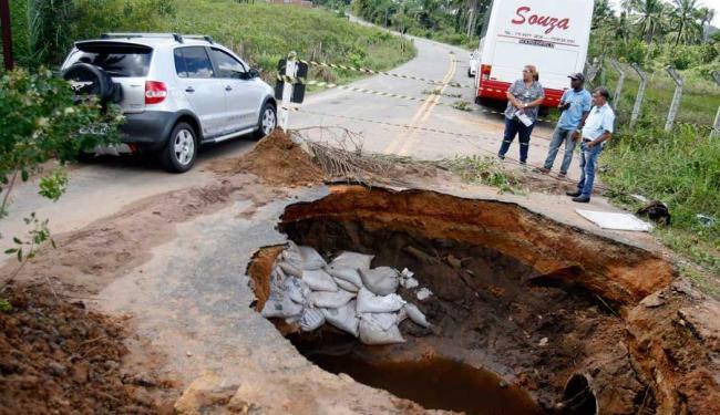 Para evitar que o restante do asfalto ceda, alguns sacos com areia foram colocados na cratera - Foto: Luiz Tito | Ag. A TARDE