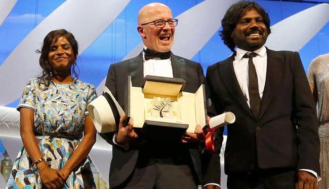 Jacques Audiard recebe o prêmio ao lado de Kalieaswari Srinivasan e Jesuthasan Antonythasan - Foto: Regis Duvignau   Agência Reuters
