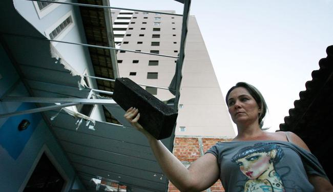 Rafaela mostra madeira que atingiu telhado de casa - Foto: Raul Spinassé   Ag. A TARDE   27.05.2015