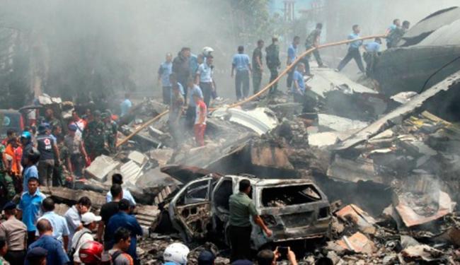 Bombeiros e pessoal de apoio inspecionam o local onde caiu um avião militar Hércules - Foto: Gilbert Manullang | AP