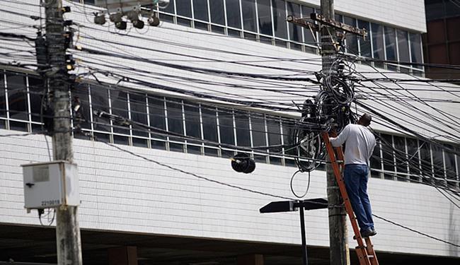 Homem sem equipamentos de proteção se arrisca em poste na Av. Tancredo Neves - Foto: Raul Spinassé l Ag. A TARDE