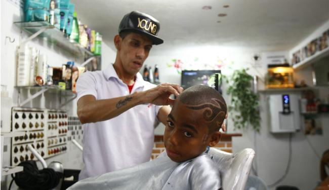 Vinicius Augusto trabalha em sua barbearia, na Liberdade - Foto: Fernando Vivas | Ag. A TARDE