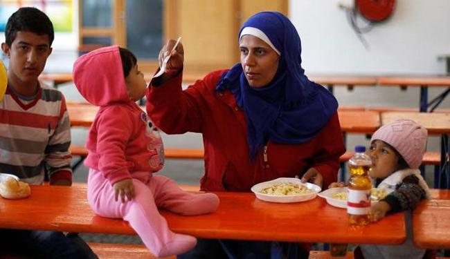 Mulher síria alimenta seu bebê em um centro para refugiados em Hamm, na Alemanha - Foto: Ina Fassbender   Agência Reuters