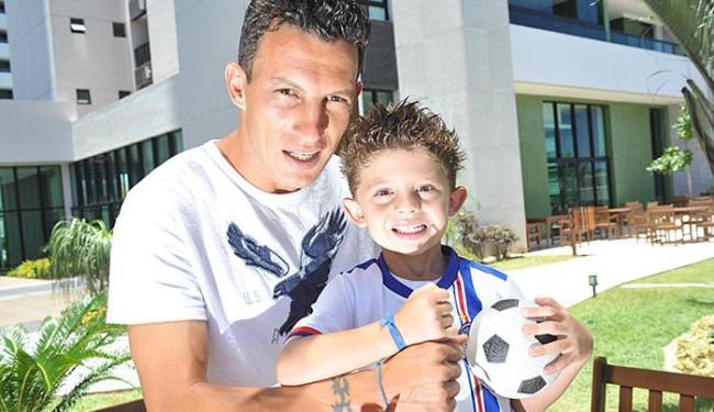 Gustavo brinca com o filho, que, de fitinha do Senhor do Bonfim e camisa do Bahia, se diz tricolor - Foto: Marco Aurélio Martins l Ag. A TARDE
