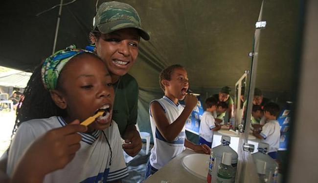 Cabo Edilene Silva ensina crianças da comunidade atendida a escovar os dentes - Foto: Fotos Joá Souza l Ag. A TARDE