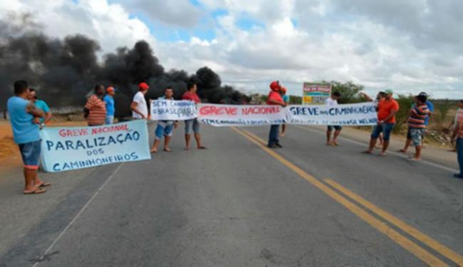 Os manifestantes estão desde as 6h20 com faixas, cartazes e queimando pneus na via - Foto: Reprodução | FR Notícias