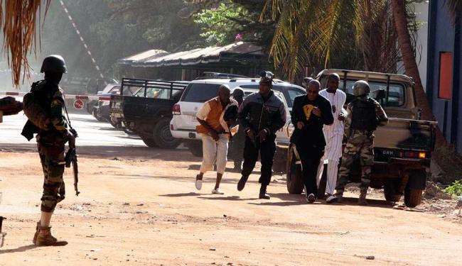Pessoas correm deixando o hotel onde acontece o sequestro - Foto: Harouna Traore | AP Photo | 20.11.2015
