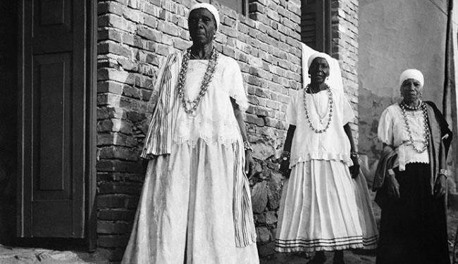 Três mulheres no Recôncavo Baiano usam bata, torço e saia numa indumentária típica de baianas - Foto: Pierre Verger | Divulgação