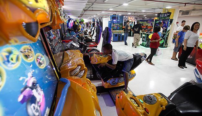 Jovem diverte-se com jogo que simula motocicleta - Foto: Raul Spinassé l Ag. A TARDE