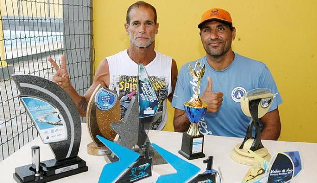 Luquine (E) e Aranha posam para foto ao lado de troféus da Travessia - Foto: Luciano da Matta l Ag. A TARDE