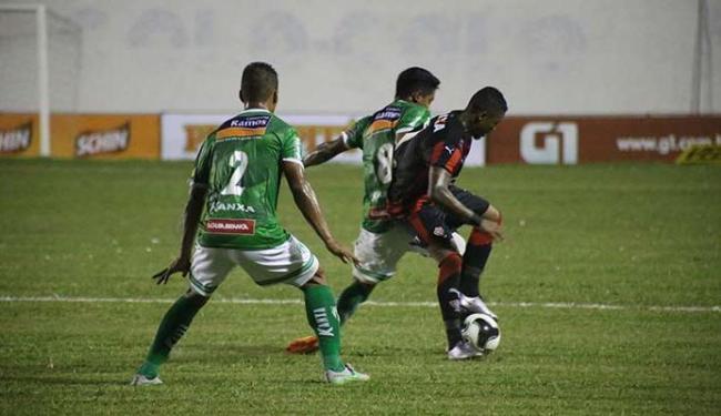 Marinho, que marcou para o Vitória, disputa a bola com dois jogadores do Conquista - Foto: José Nasal | Ag. A TARDE