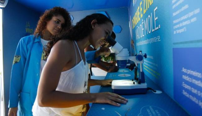 Visitante observa ao microscópio larvas mortas do mosquito vetor de três doenças - Foto: Raul Spinassé   Ag. A TARDE