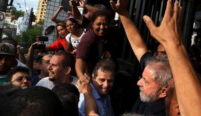 Lula acena para simpatizantes ao chegar a seu apartamento depois de ter sido detido - Foto: Paulo Whitaker | Reuters
