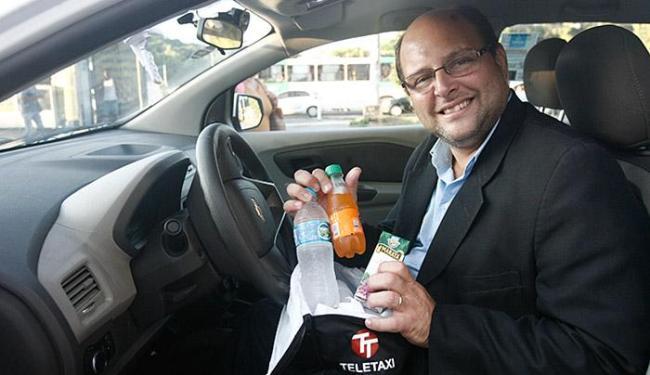 Rogério de Carvalho, da Teletáxi, exibe itens oferecidos no veículo que conduz - Foto: Margarida Neide l Ag. A TARDE