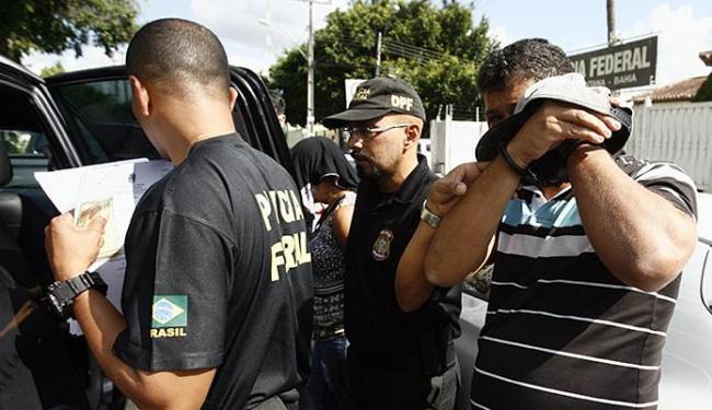 Suspeito esconde o rosto no momento em que é levado à prisão pelos policiais federais - Foto: Luiz Tito   Ag. A TARDE