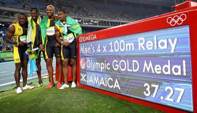 Equipe de revezamento da Jamaica, com Bolt, posa ao lado do placar com o tempo - Foto: Kai Pfaffenbach | Agência Reuters