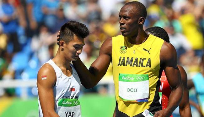 Bolt conforta atleta da Cingapura após se classificar para as semifinais - Foto: Leonhard Foeger | Ag. A TARDE