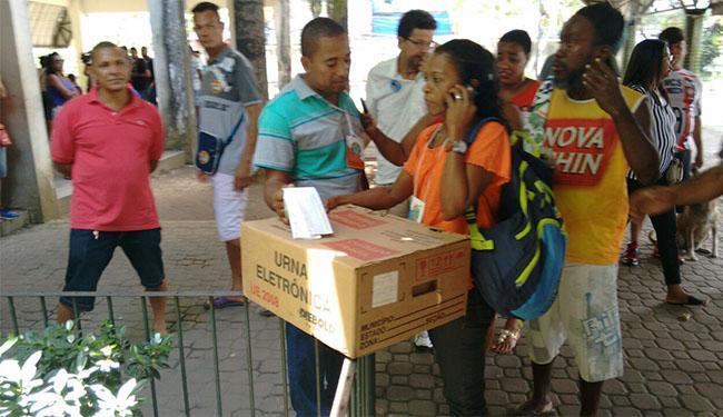 Mulher com crachá de fiscal tentava realizar a remoção da urna quando foi barrada - Foto: Luciano da Matta   Ag. A TARDE