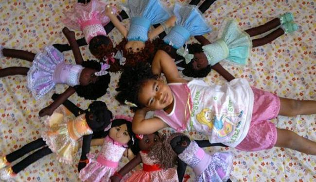 Garota posa com bonecas feitas por Patrícia e Adriana - Foto: Kanaombo Silva l Divulgação