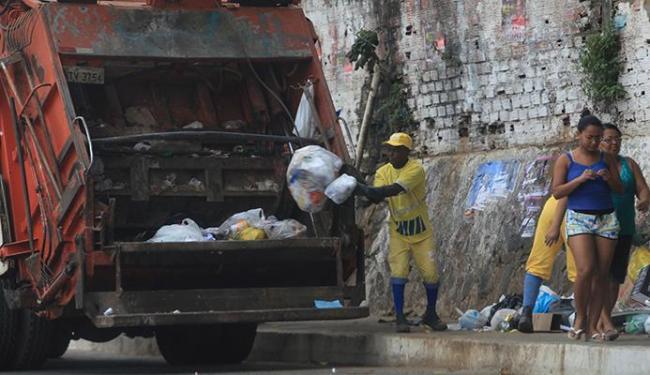 Homens recolhem sacos na calçada em Pernambués - Foto: Adilton Venegeroles | Ag. A TARDE