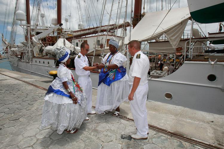 Baianas recepcionam tripulantes de embarcação amarrando-lhes no braço as tradicionais fitinhas do Bonfim - Foto: Luciano da Matta l Ag. A TARDE