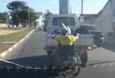 """Cadeirante """"pega ponga"""" em carro em avenida movimentada de Feira de Santana; veja"""