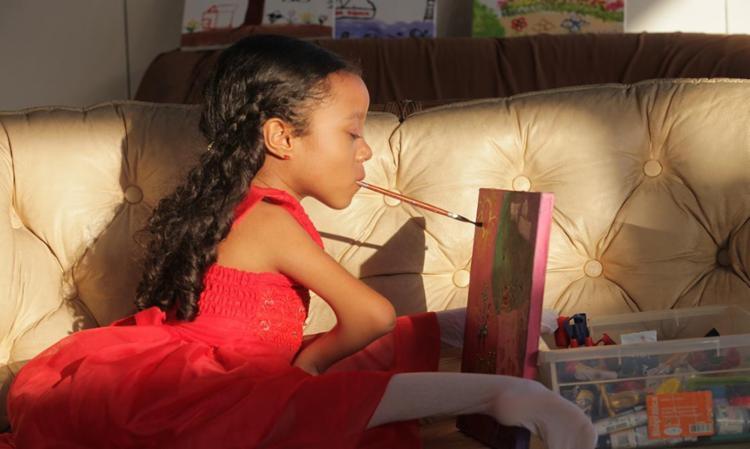 Enfermidade causa contraturas articulares, mas Luísa Hage usa mãos e pés para escrever, pintar, teclar... - Foto: Xando Pereira l Ag. A TARDE