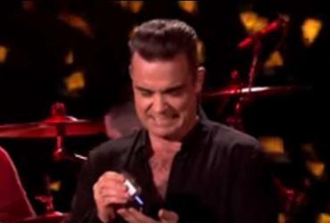 Robbie Williams limpa as mãos com álcool em gel após tocar em fãs durante show