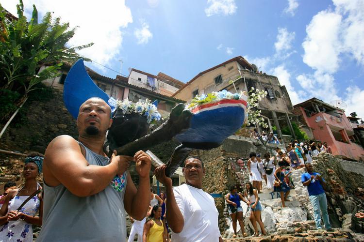 Após o cortejo passar pelos becos da comunidade, presentes foram colocados num barco lançado nas águas - Foto: Raul Spinassé l Ag. A TARDE